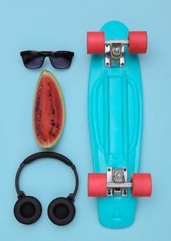 Fatia de melancia madura e acessórios de juventude hipster, placa cruiser sobre fundo azul. diversão de verão. vista do topo