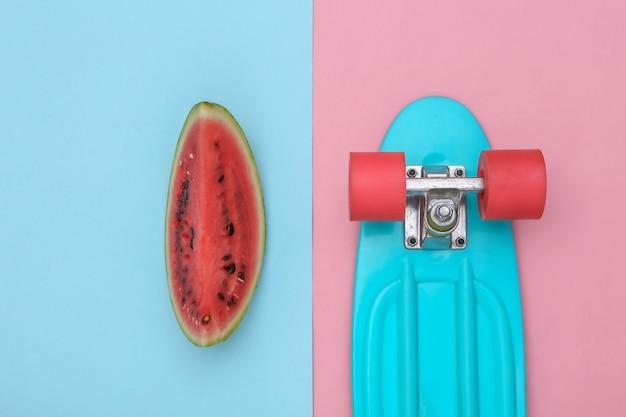 Fatia de melancia madura e placa cruzadora em fundo azul rosa. diversão de verão. vista do topo