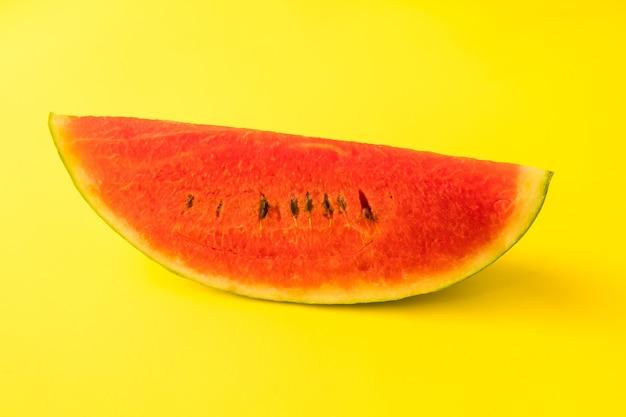 Fatia de melancia madura fresca em fundo amarelo.
