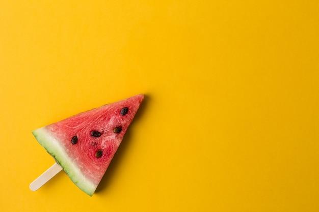 Fatia de melancia no palito de sorvete em fundo laranja