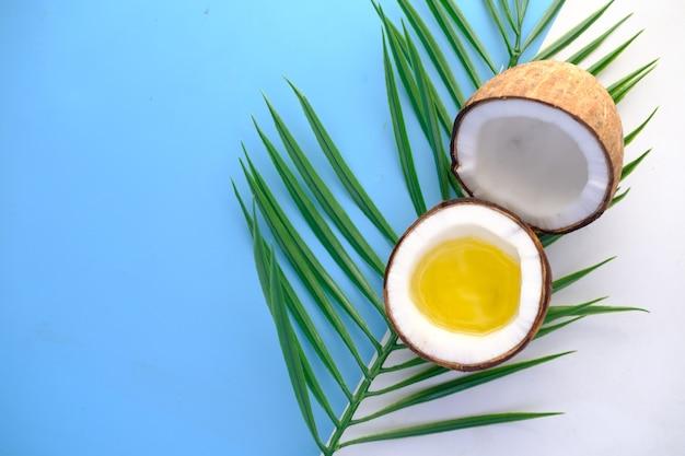 Fatia de óleo de coco fresco e folha na cor de fundo com espaço de cópia