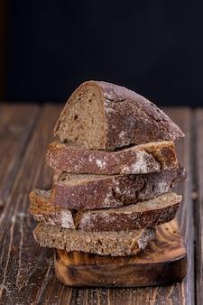 Fatia de pão caseiro fresco fatiado em uma velha mesa de madeira