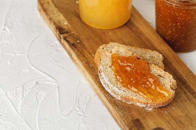 Fatia de pão coberta com geleia de frutas na tábua de madeira