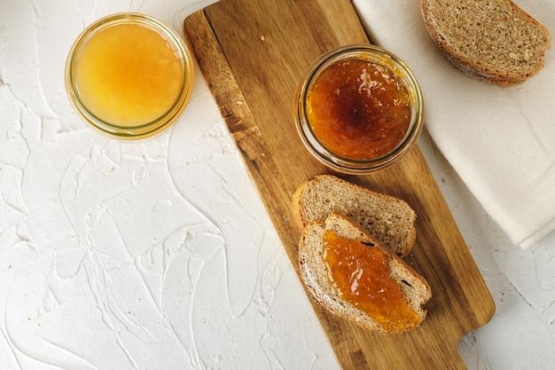 Fatia de pão coberta com geléia de frutas na tábua de madeira