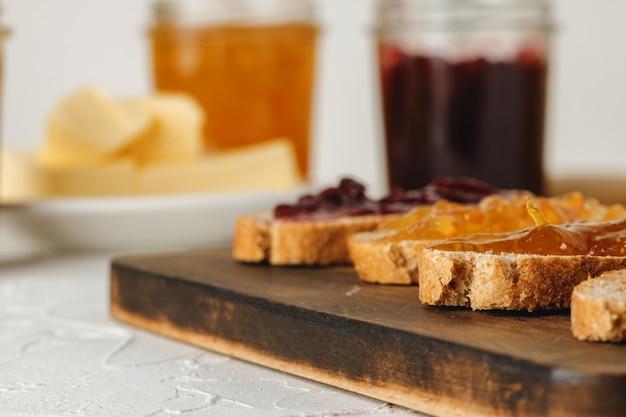 Fatia de pão coberto com geléia de frutas na placa de madeira