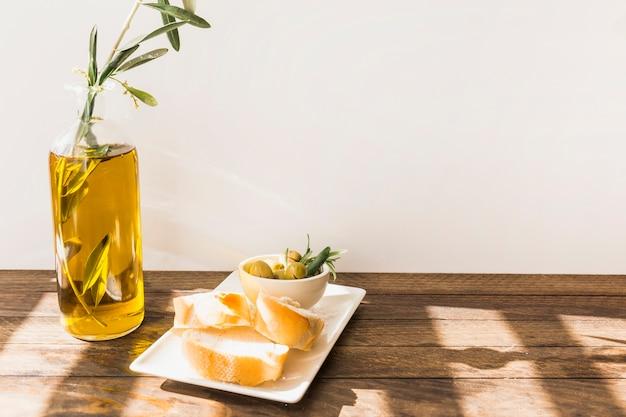 Fatia de pão com tigela de azeitonas na mesa de madeira