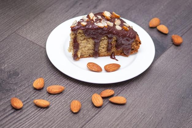 Fatia de pão de banana caseiro com chocolate, amêndoa na madeira