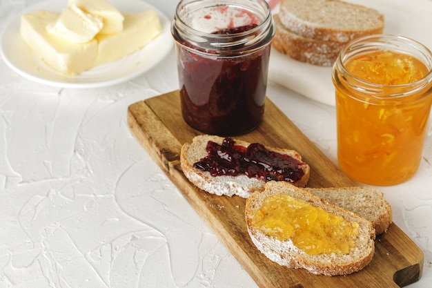 Fatia de pão fresco com manteiga e geléia na mesa de madeira