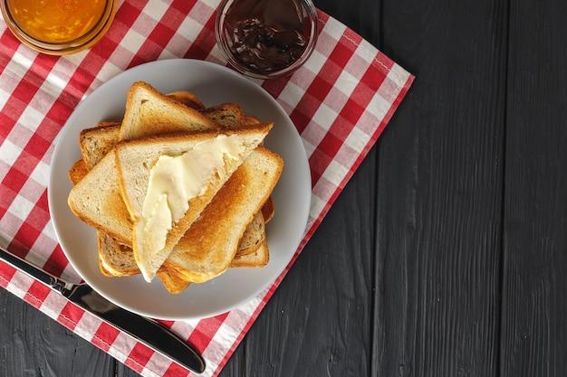 Fatia de pão fresco com manteiga e geléia na mesa