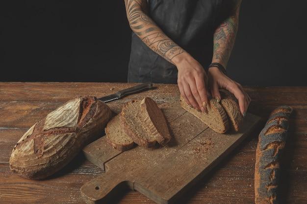 Fatia de pão fresco em mãos femininas com tatuagens em um fundo de madeira velho