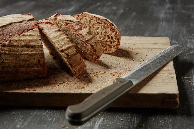Fatia de pão integral fatiado na tábua de pão de madeira com faca, em um fundo escuro