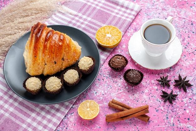 Fatia de pastelaria meia vista superior com canela e bombons de chocolate no fundo rosa.