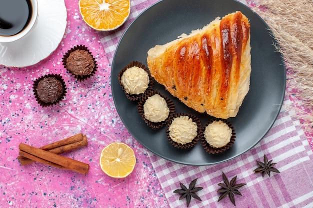 Fatia de pastelaria vista de perto superior com canela e bombons de chocolate no fundo rosa.