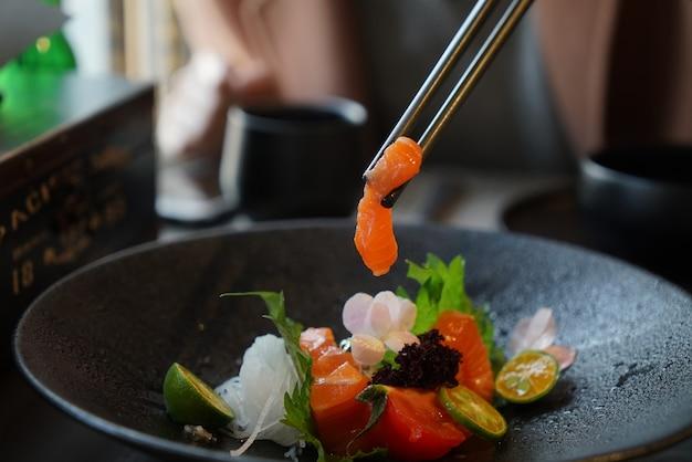 Fatia de peixes salmon fresca e crua do sashimi salmon pronta para servir no estilo japonês do alimento.