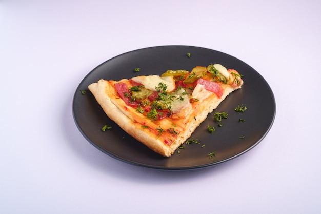 Fatia de pizza com calabresa, salame, mussarela derretida, picles e endro em chapa preta sobre fundo branco, vista de ângulo