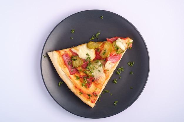 Fatia de pizza com calabresa, salame, mussarela derretida, picles e endro em chapa preta sobre fundo branco, vista superior cópia espaço