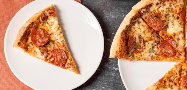 Fatia de pizza de calabresa no prato de cima
