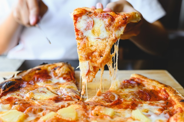 Fatia de pizza de queijo de madeira fogo na mão. tradicional pizza havaiana e salame com sabor saboroso prato de origem italiana em restaurante italiano.