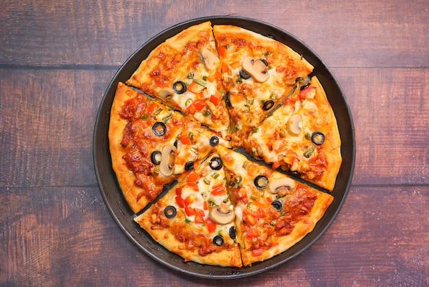 Fatia de pizza de queijo em um prato na mesa de madeira.