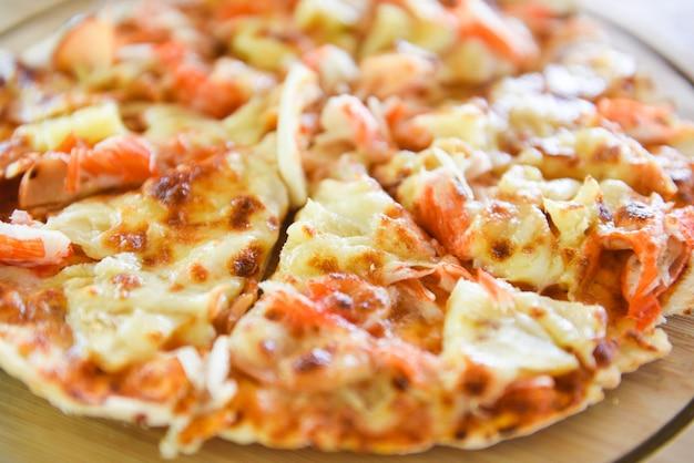 Fatia de pizza de queijo na bandeja de madeira e servida em uma mesa de madeira
