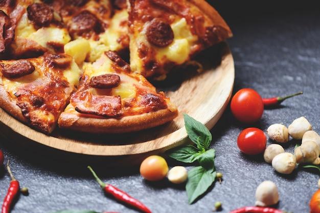 Fatia de pizza na bandeja de madeira e folhas de manjericão pimenta no escuro