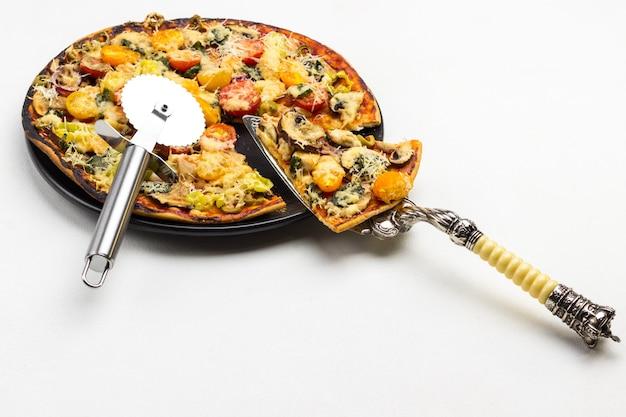 Fatia de pizza na colher e pizza na chapa preta