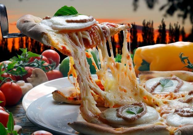 Fatia de pizza quente com derretimento de queijo com forno a lenha no fundo.