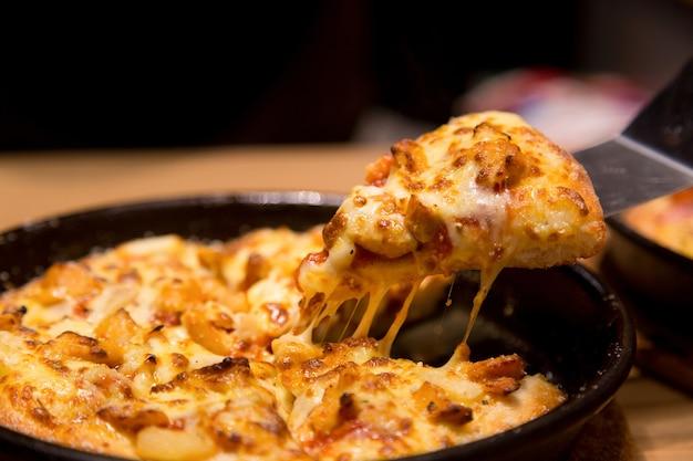 Fatia de pizza quente com queijo derretendo