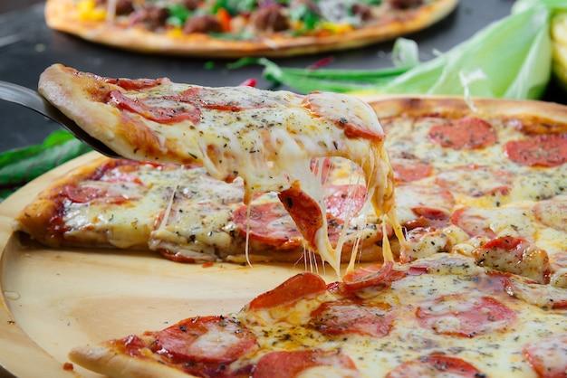 Fatia de pizza quente com queijo derretido em uma mesa de madeira escura rústica.