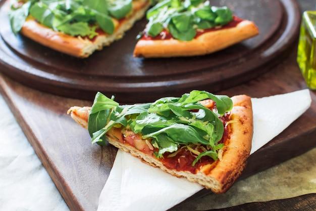 Fatia de pizza servida em papel de seda sobre a tábua de cortar