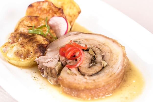 Fatia de porco assado, servido com batatas e decorado com ervas