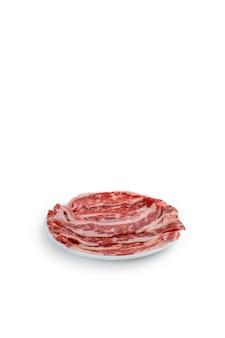 Fatia de prato curto de carne fresca na placa preta, isolada no fundo branco