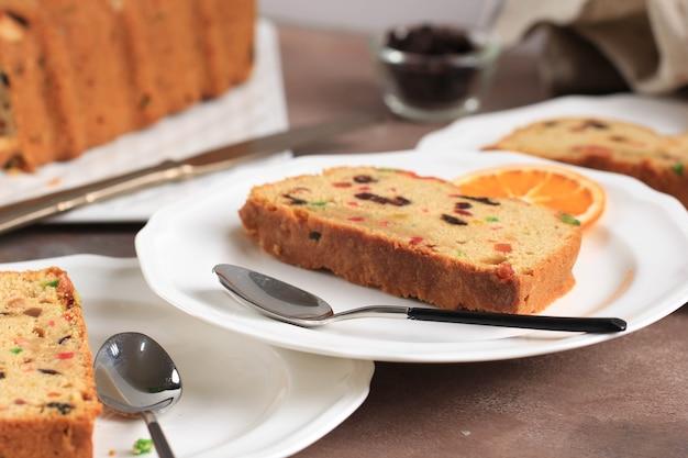 Fatia de pudim de pão de bolo inglês caseiro delicioso com frutas secas, sultanas, passas e amêndoa picada. servido durante a festa de natal ou réveillon