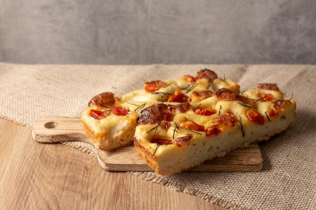 Fatia de pugliese focaccia com alecrim, azeite e tomate sobre a mesa de madeira.