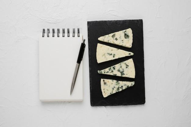 Fatia de queijo azul, disposta em ardósia preta com caderno espiral vazio e caneta sobre superfície de concreta
