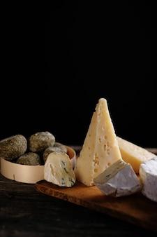 Fatia de queijo de cabra sortido na mesa de madeira
