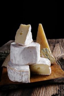 Fatia de queijo de camembert de cabra e brie na mesa de madeira escura