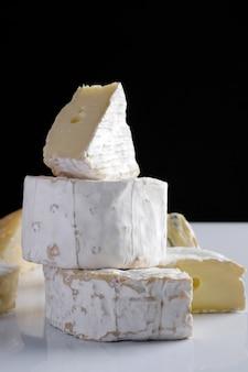 Fatia de queijo de camembert de cabra e brie na mesa escura