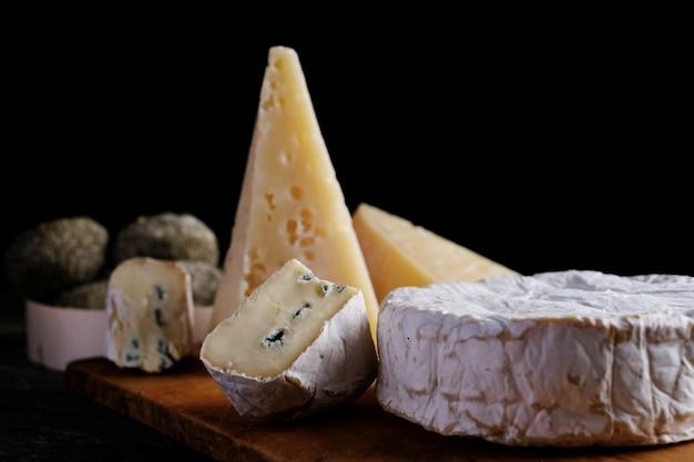 Fatia de queijo de camembert de cabra sortido na mesa de madeira