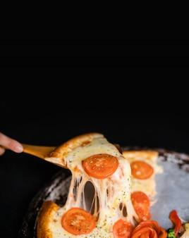 Fatia de queijo delicioso stringy levantada de margarita pizza suprema completa cozido fresco fora do forno