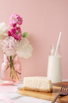 Fatia de saboroso bolo de queijo caseiro com flores e leite no fundo rosa. vista lateral vertical da torta de sobremesa orgânica saudável de verão