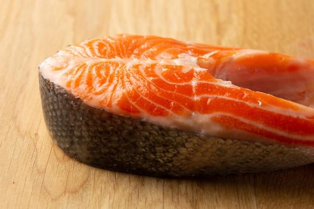 Fatia de salmão vermelho crua deitada na mesa de madeira e parecendo fresca