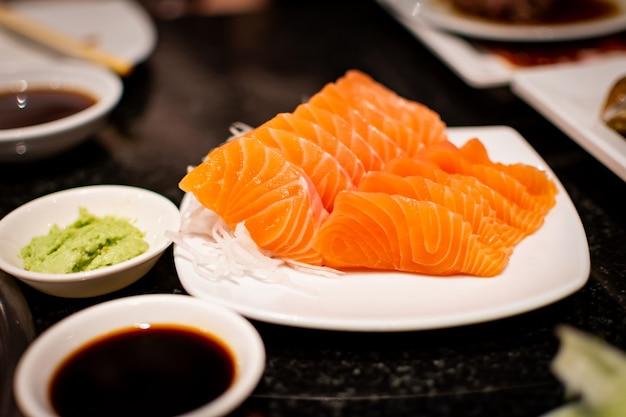 Fatia de sashimi de salmão com molho shoyu e wasabi. um famoso estilo de comida japonesa.