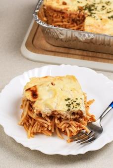 Fatia de spaghetti brulle na placa branca com garfo de madeira spaghetti brulee é spaghetti assado