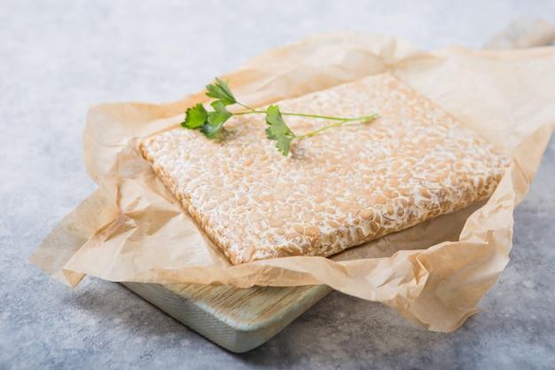 Fatia de tempeh ou tempe feita do processo de fermentação que liga a soja, é comida tradicional da indonésia e da malásia