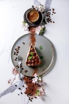 Fatia de tiramisu caseiro sem glúten tradicional sobremesa italiana polvilhada com cacau em pó, macieira florescendo, café, folhas de hortelã, grãos de café sobre a superfície de mármore branco. vista superior, configuração plana