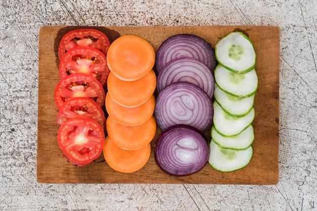 Fatia de tomate; cenouras; cebola e pepino, organizado na placa de madeira sobre o pano de fundo concreto