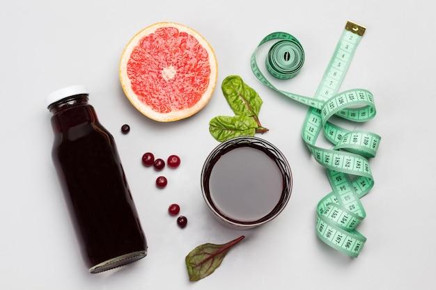 Fatia de toranja, cranberries, suco em vidro e na garrafa, fita métrica. postura plana. copie o espaço