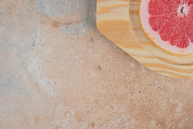 Fatia de toranja madura na placa de madeira.