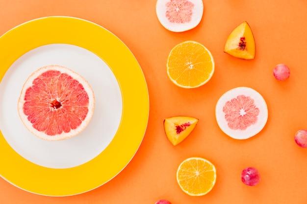 Fatia de toranja na placa branca e amarela com frutas em um pano de fundo laranja
